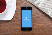 IPhone with Twitter on the screen lying on a wooden table in the — Stock Photo