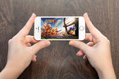 Female hands holding a white iPhone with Clash of clans on the s — Stock Photo