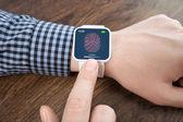 Männliche hände mit weißen smartwatch mit einem fingerabdruck auf dem geröll — Stockfoto