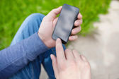 Man sitting in the park and holding touch phone — Stock Photo