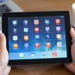Male hands holding iPad with social media app on the screen in t — Stock Photo #48409485
