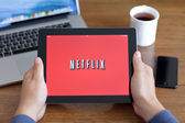Male hands holding iPad with app Netflix on the screen in the of — Stock Photo