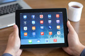 Male hands holding iPad with social media app on the screen in t — Stockfoto