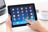 Female hands holding iPad with social media app on the screen in — Stock Photo