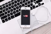 White iPhone 5s with site YouTube on the screen and headphones l — Stock Photo
