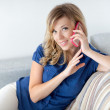 Beautiful girl sitting on a sofa and talking on the phone — Stock Photo #49345239