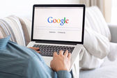 Man sitting at the MacBook retina with site Google on the screen — ストック写真