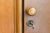 Wooden door handle and key in a keyhole — Stock Photo