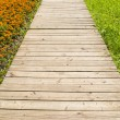 Wooden road through grass and flowers — Stock Photo