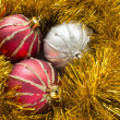 Three christmas balls in tinsel — Stock Photo