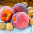 Three Peaches and Some Walnuts — Stock Photo