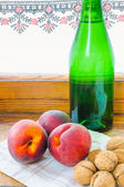Peaches and Walnuts with Bottle — Stock Photo