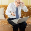 Stock Photo: Surprised Senior Businessmwith Computer