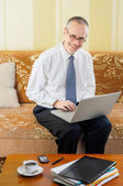 Friendly Senior Businessman with Computer — Stock Photo
