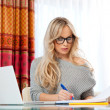 Photo: Attractive woman wit laptop at home