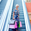 Woman on escalator stairs in shopping — Stock Photo #19679549