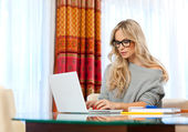 Attractive woman writing on laptop — ストック写真