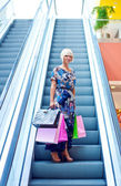 Woman on escalator stairs in shopping — Stock Photo