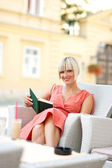 Woman with book in cafe — Stock Photo