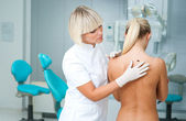 Doctor examining woman skin — Stockfoto