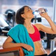 Woman in gym drink water - Stock Photo