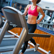 Woman in gym running on track - Stock Photo