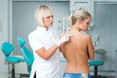 Medico cerca talpa sulla pelle donna — Foto Stock
