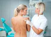 Doctor examining woman skin — Stock Photo