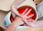 Vrouw hand in paraffinebad — Stockfoto