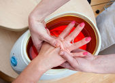 Woman hand in paraffin bath — Stock fotografie