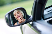 Woman driver putting lipstick — Stock Photo