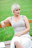 Attractive woman sitting on bench — Stock Photo