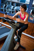 Woman in gym on bycicle — Stock Photo