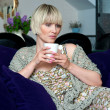 Woman with coffee on sofa — Stock Photo #19781427