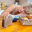 Woman sleepinh at breakfast table — Stock Photo #19781775