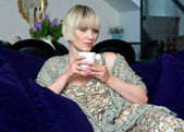 Woman with coffee on sofa — Stock Photo
