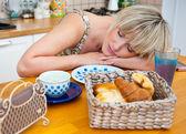 Woman sleepinh at breakfast table — Stock Photo