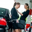 Two girlfriends on gas station - Stock Photo
