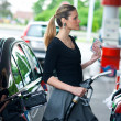 Woman holding money on gas station — Stock Photo #19794665