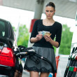 Stock Photo: Womcounting money on gas station
