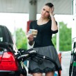 Womcounting money on gas station — Stock Photo #19794729