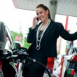 Stock Photo: Womin gas station talking to mobile phone