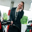 Womin gas station talking to mobile phone — Stock Photo #19795053