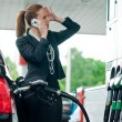 Womin gas station talking to mobile phone — Stock Photo #19795087