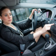 Woman driving and changing radio station — Stock Photo #19795293