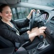 Woman driving and changing radio station — Stock Photo #19795329