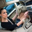 Woman driving and changing radio station — Stockfoto