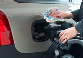 Woman holding money on gas station — Stock Photo