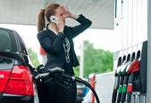 Vrouw in gas station praten met mobiele telefoon — Stockfoto