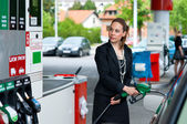 Elegant woman in gas station — Stock Photo